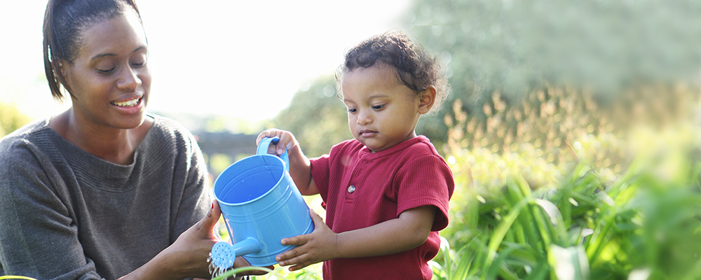 mother watering plants wiht toddler son