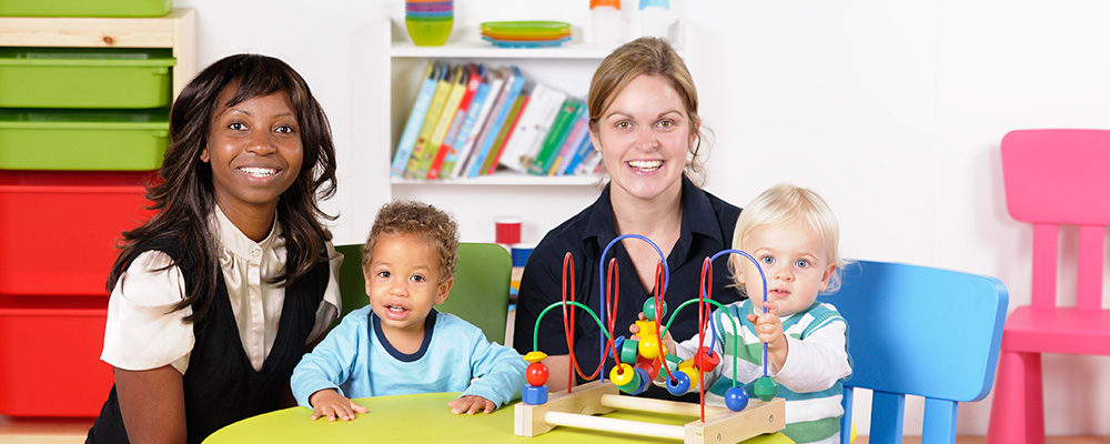 two teachers with toddlers playing with toys at a table