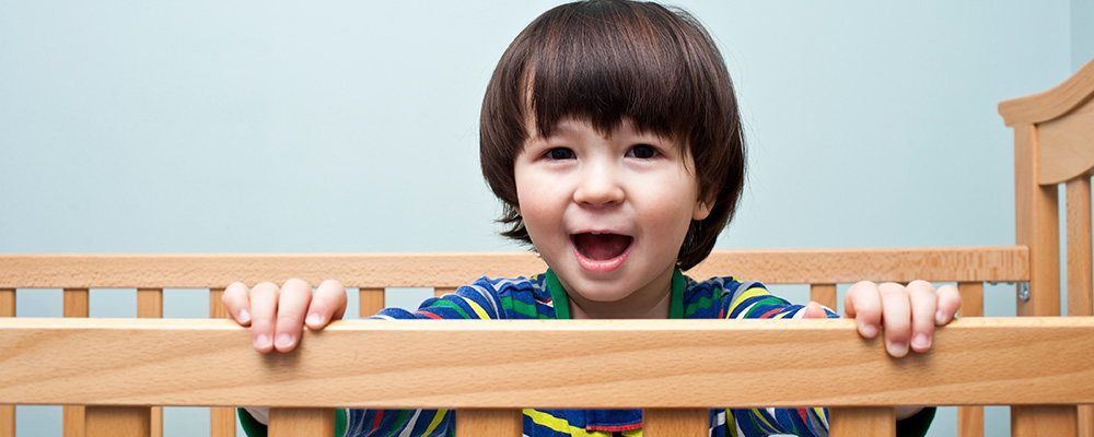 o two-year-old boy standing up in his crib
