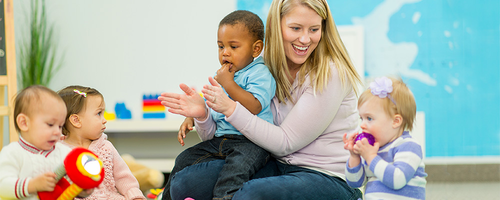 teacher sitting on the floor clapping hands with toddlers
