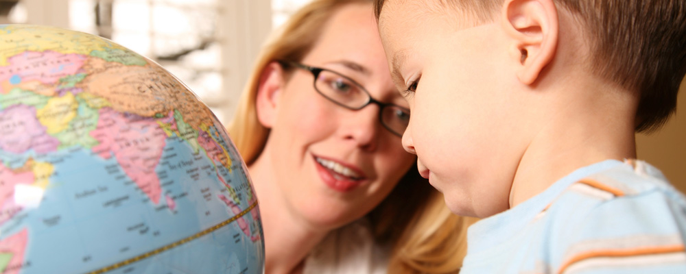 teacher and preschool boy looking at a globe