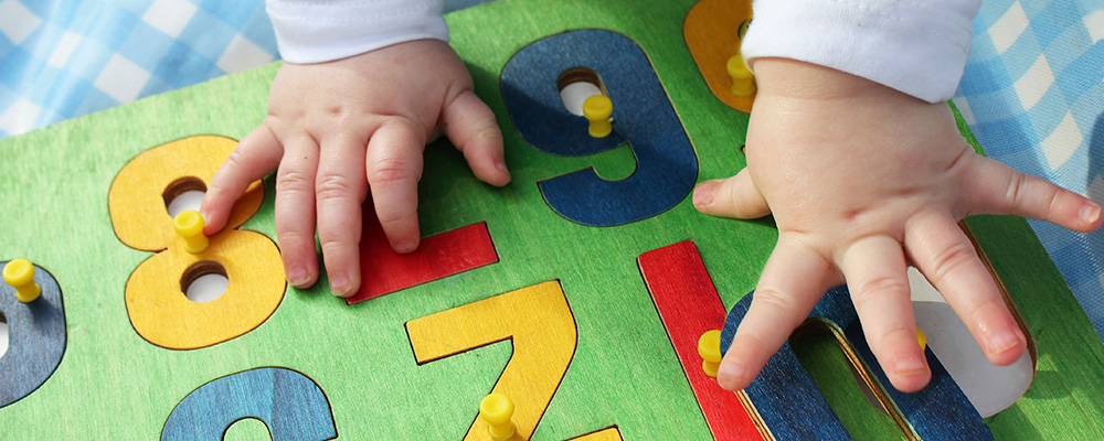 toddler hands working on a wooden puzzle of numbers