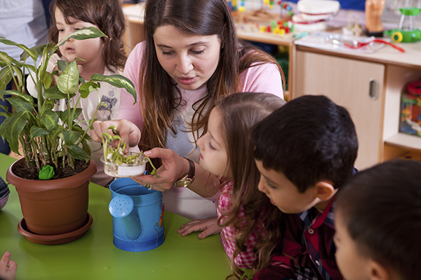 science teacher helping preschoolers with plants