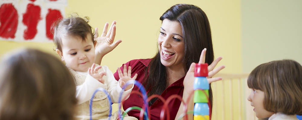 happy teacher playing with toddlers